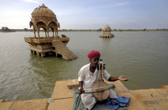Bachu Khan, a Rajasthani artisan plays music for tourists at Gadisar Lake at Jaisalmer
